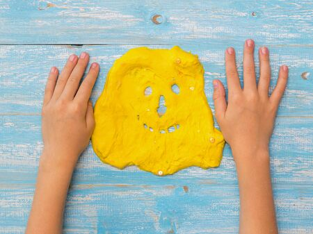 The childs hands on the table next to the face of a yellow slime. Toy antistress. Toy for the development of hand motor skills.