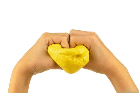 The child is holding a heart of yellow slime isolated on a white background. Toy antistress. Toy for the development of hand motor skills.