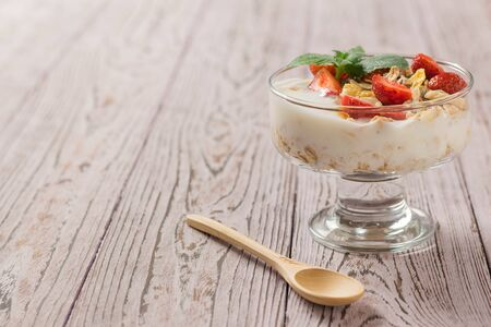 Pieces of fresh strawberries in yogurt with mint on a wooden table. Delicious, healthy and nutritious natural food.