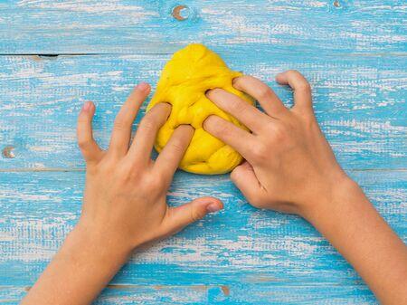 La fille pétrit la boue jaune sur une table en bois bleue. Jouet antistress. Jouet pour le développement de la motricité de la main.