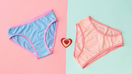 Blue and pink panties and red heart on blue and pink background. The concept of meeting lovers. Underwear. The view from the top. Beautiful lingerie. Flat lay.