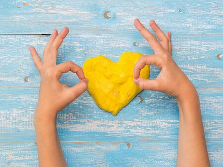 The child shows a hand that all is well on the background of yellow hearts. Toy antistress. Toy for the development of hand motor skills. 写真素材