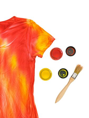 Two open cans of paint, a brush and a t-shirt in the style of tie dye on a white background. Staining fabric in tie dye style.