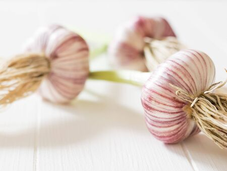 Three heads of fresh, large garlic on a white table. Healthy natural seasoning. Component of traditional medicine.