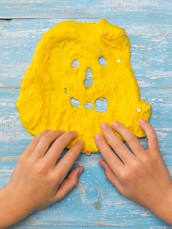 The child draws teeth on a face of yellow slime on a wooden table. Toy antistress. Toy for the development of hand motor skills. 写真素材