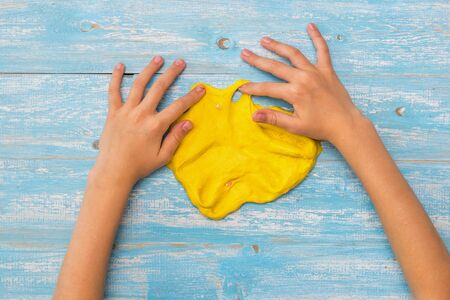 The child makes crafts from yellow slime on the table. Toy antistress. Toy for the development of hand motor skills.