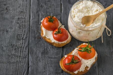 A jar of cottage cheese and bread with cottage cheese and tomatoes on the table. The concept of a healthy diet. 写真素材