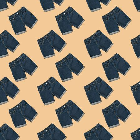 Seamless pattern of blue denim shorts on beige background. Fashionable unisex clothing. Summer denim clothing. 写真素材