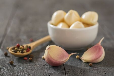Garlic and pepper on a black wooden table. Healthy natural seasoning. Component of traditional medicine.