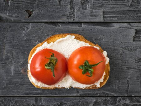 Toasted bread with cottage cheese and tomatoes on a wooden table. The concept of a healthy diet. The view from the top flat lay. 写真素材