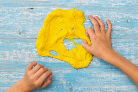 The child stretches the mouth of the yellow slime with his right hand. Toy antistress. Toy for the development of hand motor skills. 写真素材