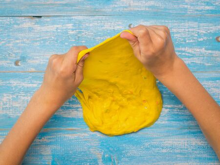 The child stretches the yellow slime thinly on the table. Toy antistress. Toy for the development of hand motor skills.