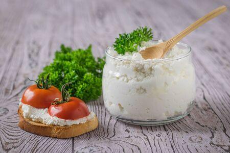 Een pot en brood met kwark en tomaten op een roze houten tafel. Het concept van een gezond dieet.