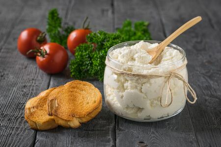 A jar of cottage cheese, tomatoes and bread on a wooden table. The concept of a healthy diet.