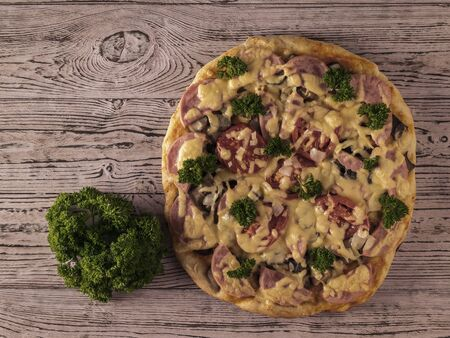 Toned image of a pizza with a bunch of parsley on a wooden table. Traditional Italian cuisine. The view from the top. Stockfoto
