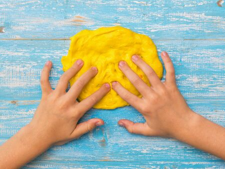 The child kneads with his fingers a circle of yellow slime on a blue table. Toy antistress. Toy for the development of hand motor skills.