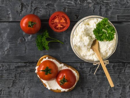 Bread with tomatoes and a jar of cottage cheese on a black wooden table. The concept of a healthy diet. Flat lay. The view from the top. Stockfoto