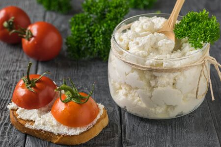 Bread with tomatoes and a jar of cottage cheese on a black wooden table. The concept of a healthy diet. Stockfoto