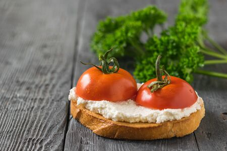 Fresh tomatoes with cottage cheese on a piece of bread on a wooden table. The concept of a healthy diet. Stockfoto
