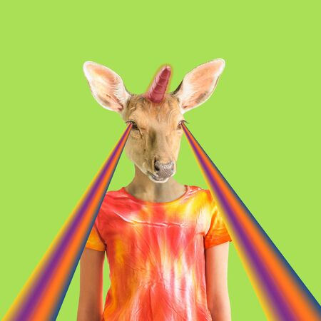 Modern art collage.The figure of a girl with a deer head with a unicorn horn on a green background with rays from the eyes. Minimalism. Stock Photo