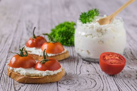 Bread with fresh cottage cheese and cherry tomatoes on a wooden table. The concept of a healthy diet. Stockfoto