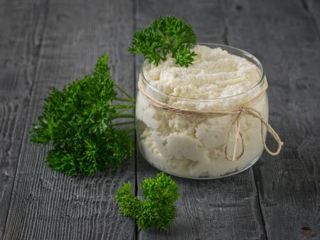 A jar of fresh cottage cheese with curly parsley on a wooden table. The concept of a healthy diet.