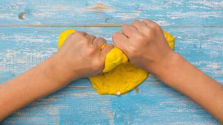 The childs hands crumple bright yellow slime on a wooden table. Toy antistress. Toy for the development of hand motor skills.