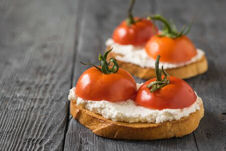 Two pieces of toasted bread with cottage cheese and tomatoes on the table. The concept of a healthy diet.