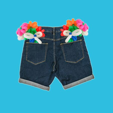 Contemporary art collage. Bouquets of balloons in the back pockets of mens jeans. The concept of adult gifts. Stock Photo