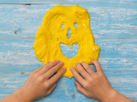 The child makes a funny face of yellow slime on a wooden table. Toy antistress. Toy for the development of hand motor skills.