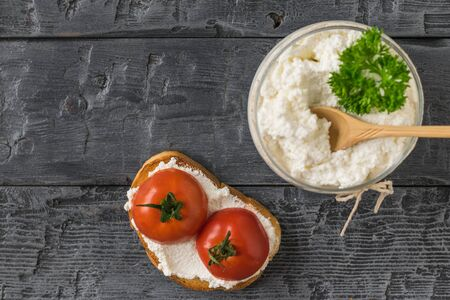 Breakfast is made of toasted bread, cottage cheese and tomatoes on a wooden table. The concept of a healthy diet. Flat lay. The view from the top. Stockfoto