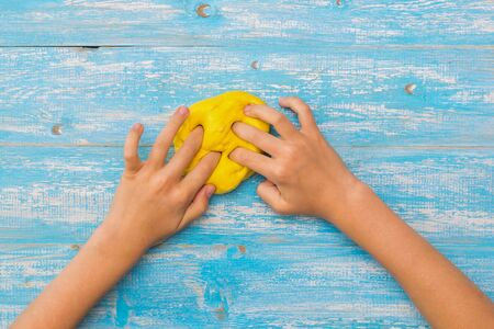 Girl kneads a ball of yellow slayma on blue wooden table. Toy antistress. Toy for the development of hand motor skills.