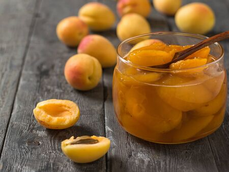 Jam of ripe apricots in a glass jar on a wooden table. Freshly made homemade jam.
