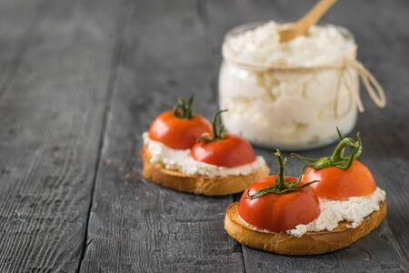 Fried bread, cottage cheese and tomato halves on a wooden table. The concept of a healthy diet. 写真素材 - 129734879