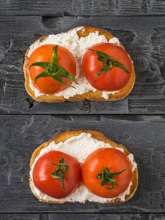 Two loaves of cottage cheese and tomato halves on a black table. The concept of a healthy diet. The view from the top flat lay. 写真素材 - 129734989