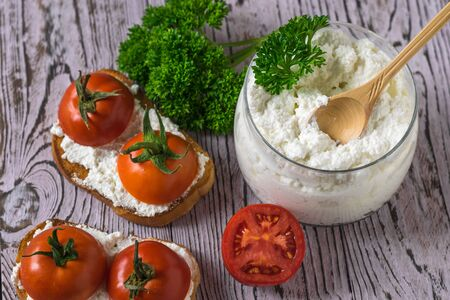 Tomato halves, cottage cheese, bread and herbs on a wooden table. The view from the top. The concept of a healthy diet.