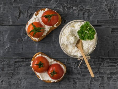 Two pieces of bread with cottage cheese and tomatoes on a wooden table. The concept of a healthy diet. Flat lay. The view from the top. 写真素材 - 129735004