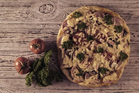 Toned image of a pizza with a bunch of parsley on a pink wooden table. Traditional Italian cuisine. The view from the top.