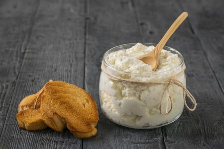 Toasted bread with cottage cheese and a wooden spoon on a rustic wooden table. The concept of a healthy diet. Stockfoto