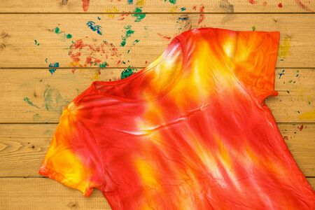 T-shirt painted in the style of tie dye on a wooden table for painting. Staining fabric in tie dye style. Flat lay.
