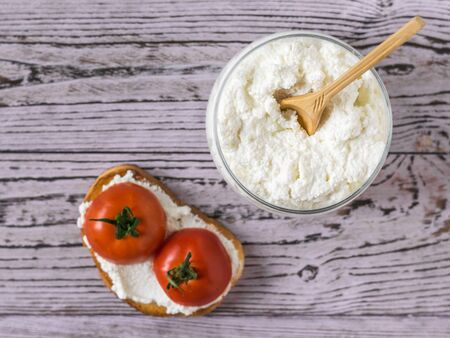 Cottage cheese in a jar and bread with cottage cheese and tomatoes on a wooden table. The concept of a healthy diet. The view from the top flat lay. Stockfoto