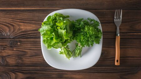 Fresh greens on a white plate and a fork on a wooden table. The concept of healthy eating. Flat lay. Stockfoto