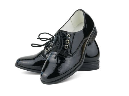 Fashionable black womens patent leather shoes isolated on white background. Fashionable school shoes. Фото со стока