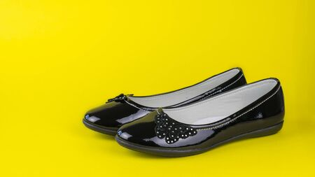 Low fashion womens shoes on a yellow background. Fashionable school shoes. Фото со стока