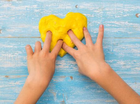 The child sculpts a heart of yellow slime on a blue table. Toy antistress. Toy for the development of hand motor skills.