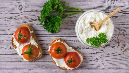 Bread with cottage cheese and tomato halves on a wooden table. The concept of a healthy diet. The view from the top flat lay.