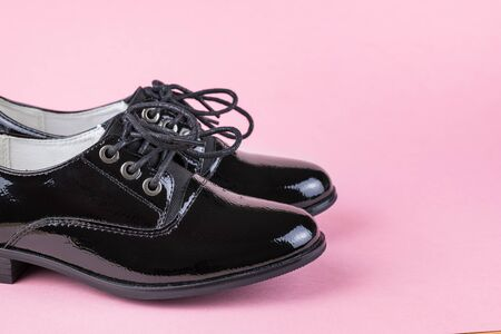 A pair of fashionable black womens shoes on a pink background. Fashionable school shoes.