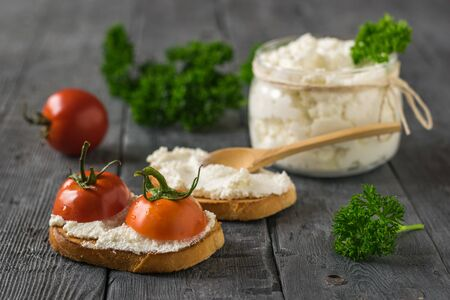 Cherry tomatoes and cottage cheese on a wooden table. The concept of a healthy diet. 写真素材 - 129735177