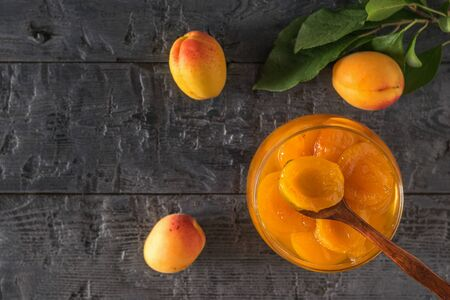 Ripe apricots and a wooden spoon in apricot jam on a wooden table. Freshly made homemade jam.