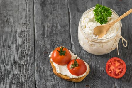 Cottage cheese in a jar with bread and cherry tomatoes on the table. The concept of a healthy diet. Stockfoto
